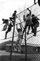 Children climbing on school playground fence