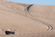 A dune buggy waits before ascending the winding path cut into the sand that leads to the miles of dunes outside of Huacachina, Peru.