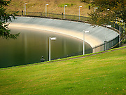 Reservoir 5, one of three open reservoirs at Mount Tabor Park and of five total in Portland.  In 1903, John Charles Olmsted of the Massachusetts-based landscape design firm Olmsted Brothers recommended that a city park be developed at Mount Tabor.  Portland Parks Superintendent Emanuel T. Mische, who had worked at Olmsted Brothers, consulted with Olmsted on the park layout and integration of the reservoirs into the park design. The 3 open reservoirs in Mount Tabor Park, with their ancillary structures, were placed in the National Register of Historic Places on January 15, 2004.  Environmental Protection Agency (EPA) regulation: Long Term 2 Enhanced Surface Water Treatment Rule, referred to as the LT2 rule imposes new requirements that open water reservoirs be covered, buried or additionally treated.  This applies to Portland's five open reservoirs and to the unfiltered Bull Run source supplying them. Mount Tabor Park, Portland, Oregon, USA.