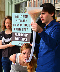 A PETA anti fois gras demonstration outside Fortnum and Mason in London, showing a women pretending to be 'force fed', Wednesday, 7th August 2013 Photo by: Nils Jorgensen / i-Images