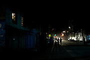 People walk along the street at night in Kargil, Jammu and Kashmir, India