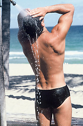 man in an outdoor shower at the beach