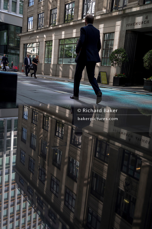 Financial services people walk through reflected light from a nearby skyscraper in the City of London, the capital's financial district aka the Square Mile, on 17th May 2018, in London, UK.