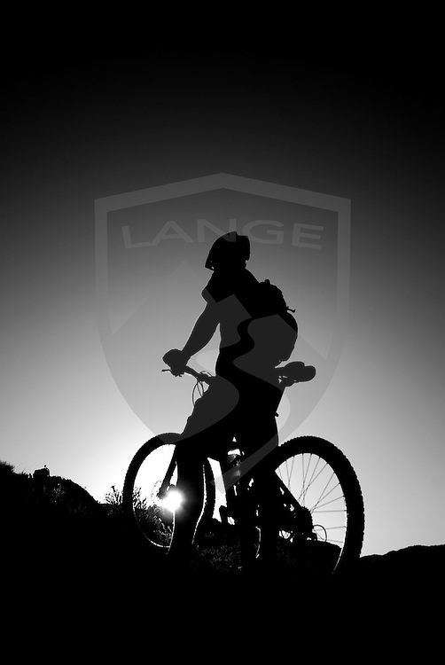 a mountain biker stands against a clear sky with the sunshine creating a silhouette in black and white at the white mesa bike trails of new mexico.