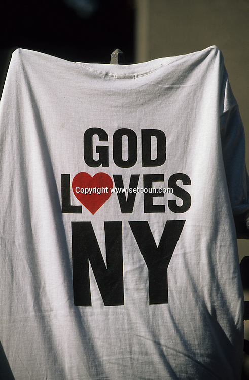 New York.  God loves america tee shirt. paintings drawings and testimony on memorials around the destroyed world trade center  and in the city, after the attack:  New York  Usa /   dessin, affiches et temoignages sur les memorial autour du world trade center detruit. et dans la ville apres l'attaque,   New York