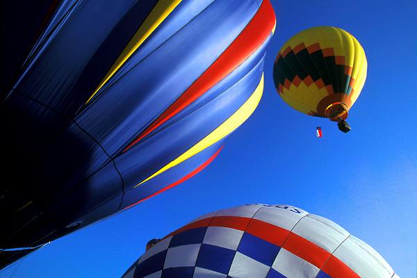 Stock photo of three hot air balloons in air at the Ballunar Liftoff Festival in Houston Texas