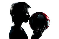 one caucasian young teenager silhouette boy or girl kissing soccer football portrait in studio cut out isolated on white background