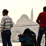 Two fishermen cast their lines in the Golden Horn on the waterfront near the Karakoy Fish Market in Istanbul near the Galata Bridge. In the disance is the Suleymaniye Mosque.