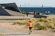 A runner wearing an orange shirt jogs amongst the sand dunes at Amager Strand (Amager Beach) in Copenhagen, Denmark. In the background looms the Øresund Bridge between Malmø in Sweden and Denmark<br /> <br /> © Travel Photographer in Copenhagen Matthew James