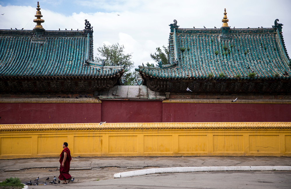 "A Buddhist monk walks the grounds of the Gandantegchinlen Monastery, known as the Gandan Monastery, a Tibetan-style monastery in the Ulaanbaatar Mongolian, on July 23, 2012.  The Tibetan name translates to the ""Great Place of Complete Joy."" It currently has over 150 monks in residence. The Gandan Monastery was renovated in 1990 following the collapse of the communist government in Mongolia. © 2012 Tom Turner Photography."