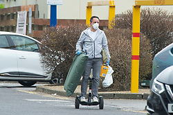 ©Licensed to London News Pictures 19/03/2020<br /> Maidstone, UK. Coronavirus threat. A shopper riding his Segway home wearing a protective face mask and gloves in Maidstone, Kent. Photo credit: Grant Falvey/LNP