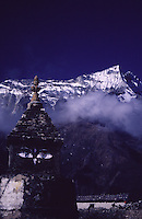 A Buddhist stupa in the town of Namche Bazaar perched below a snowy Himalayan mountain range.