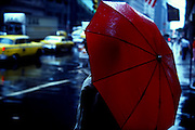 Red umbrella and black leather jacket standing in the rain in front of Grand Central Station in Manhattan, New York City, New York. The streets are wet and yellow New York Taxi cabs.