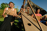 Mayan father and two sons in Midway Village in SouthernBelize play the violin, harp, and mandolin outside their thatched hut in their traditional Mayan village.