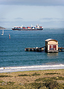 shed on Queenscliff Pier with passing container ship