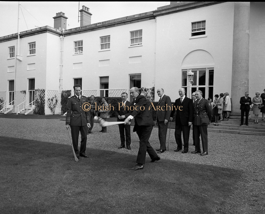 Having had a few lessons from All-Ireland winner Jack Lynch, King Baudouin takes a puck at the sliotar in the grounds of the Aras. Watching on are (l to r)Sean O Siochain, GAA President, Minister Frank Aiken, President Eamon  de Valera, and An Taoiseach Jack Lynch.<br /> 17.05.1968