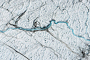 Meltwater flows thru a low area of the Greenland ice sheet that had previously been deposited dark with cryoconite, 60km southeast of Ilulissat, August, 2014. The presence of cryoconite, or ash and soot deposited on top of the ice sheet, triples the melt rate atop the ice sheet.