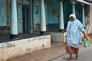 Woman walking past an old home in Nagore, South India.