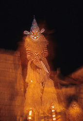 Africa, Zimbabwe, traditional masked dancer on stilts (of Makishi tribe) at night