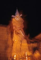 Africa, Zimbabwe, traditional masked dancer on stilts (of Makishi tribe) at night