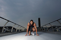 Athlete crouching at starting blocks on footbridge Millennium Bridge London England