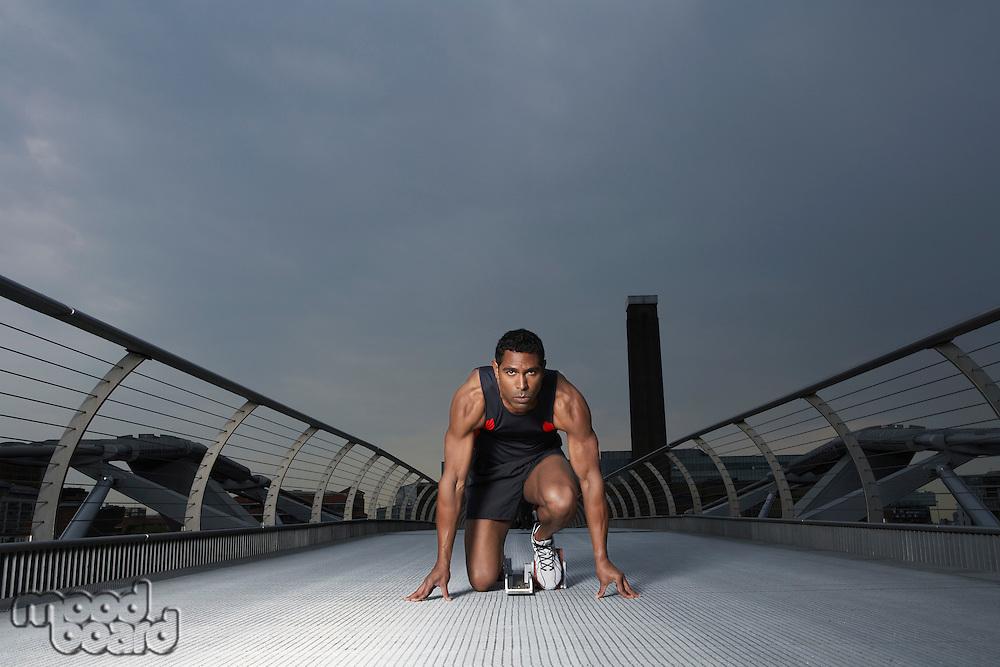 Athlete crouching at starting blocks on footbridge Millennium Bridge London England