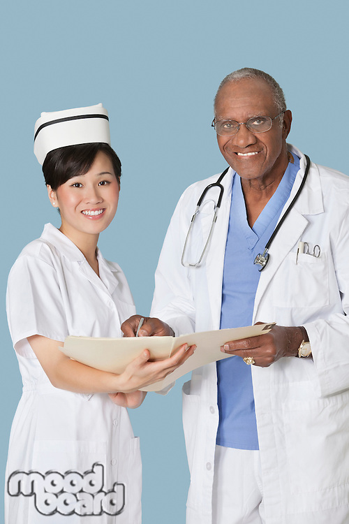Portrait of happy medical professionals with medical report against light blue background