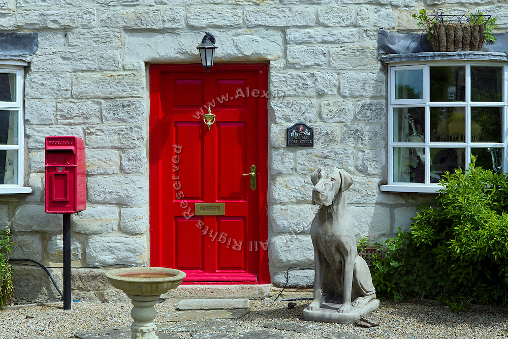 A dog statue is standing next to a red door to a home in Kilburn, Yorkshire, England, United Kingdom.