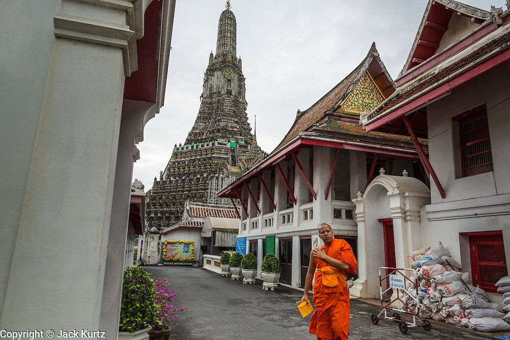 "23 SEPTEMBER 2013 - BANGKOK, THAILAND: A Buddhist monk walks out from the monk housing area to the main prayer hall at Wat Arun in Bangkok. The famous central prang of the temple is in the background. The full name of the temple is Wat Arunratchawararam Ratchaworamahavihara. The outstanding feature of Wat Arun is its central prang (Khmer-style tower). The world-famous stupa, known locally as Phra Prang Wat Arun, will be closed for three years to undergo repairs and renovation along with other structures in the temple compound. This will be the biggest repair and renovation work on the stupa in the last 14 years. In the past, even while large-scale work was being done, the stupa used to remain open to tourists. It may be named ""Temple of the Dawn"" because the first light of morning reflects off the surface of the temple with a pearly iridescence. The height is reported by different sources as between 66,80 meters and 86 meters. The corners are marked by 4 smaller satellite prangs. The temple was built in the days of Thailand's ancient capital of Ayutthaya and originally known as Wat Makok (The Olive Temple). King Rama IV gave the temple the present name Wat Arunratchawararam. Wat Arun officially ordained its first westerner, an American, in 2005. The central prang symbolizes Mount Meru of the Indian cosmology. The temple's distinctive silhouette is the logo of the Tourism Authority of Thailand.           PHOTO BY JACK KURTZ"