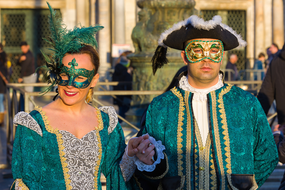 A man and a woman are seen walking through St Mark's square during the 2017 Venice Carnival