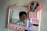Portrait of a factory worker from Henan in his simple home in Huizhou.
