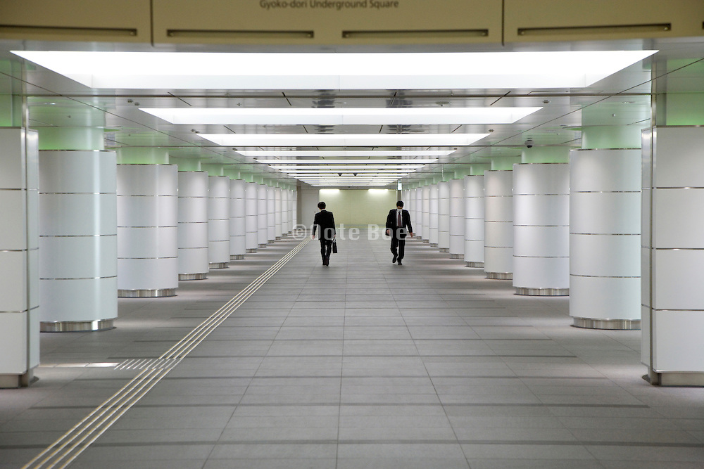 businessmen walking in opposite direction through an corridor