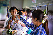 15 JUNE 2013 - YANGON, MYANMAR:  A betel vendor, left, jokes with a customer on the Yangon Circular Train. Many Burmese chew betel, a mildly stimulating leaf which stains the teeth red. The Yangon Circular Railway is the local commuter rail network that serves the Yangon metropolitan area. Operated by Myanmar Railways, the 45.9-kilometre (28.5 mi) 39-station loop system connects satellite towns and suburban areas to the city. The railway has about 200 coaches, runs 20 times and sells 100,000 to 150,000 tickets daily. The loop, which takes about three hours to complete, is a popular for tourists to see a cross section of life in Yangon. The trains from 3:45 am to 10:15 pm daily. The cost of a ticket for a distance of 15 miles is ten kyats (~nine US cents), and that for over 15 miles is twenty kyats (~18 US cents). Foreigners pay 1 USD (Kyat not accepted), regardless of the length of the journey.    PHOTO BY JACK KURTZ