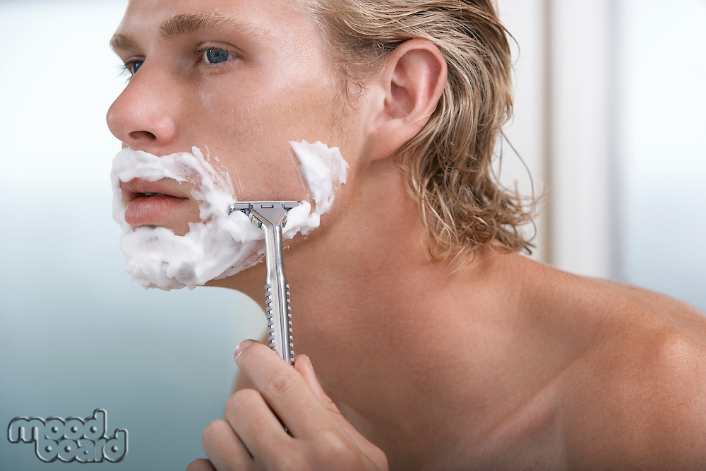 Man shaving face in bathroom close-up