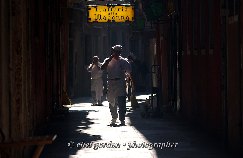 Shopkeepers stroll in the morning light  in Venice, Italy. April 2002.