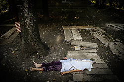 The body of a dead local girl, 11 year old, lies near a damaged block of flats after Ukranian army shelling in downtown of Donetsk, Ukraine, 23 August 2014. Residential areas in several districts of Donetsk, including the central part of the city, suffered from artillery fire, five people was killed and 15 wounded, the press centre of Donetsk city Council reported.
