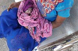 April 27, 2017 - MAHARASHTRA, INDIA - MAHARASHTRA, INDIA- APRIL, 23, 2017: Chandana Saha, 26 pictured holding her new born baby at railway station in Mumbai city in Maharashtra, India.....Chandana was seven months pregnant when she was travelling on a train. She went to use the toilet and suddenly went into labour. Three ladies came to help her but her baby had fallen through the toilet and onto the railway track.....The baby miraculously survived but died 12 hours later. Sadly the mother. Chandana, also died two days later. ....Pictures supplied by: Cover Asia Press (Credit Image: © Cover Asia via ZUMA Press)