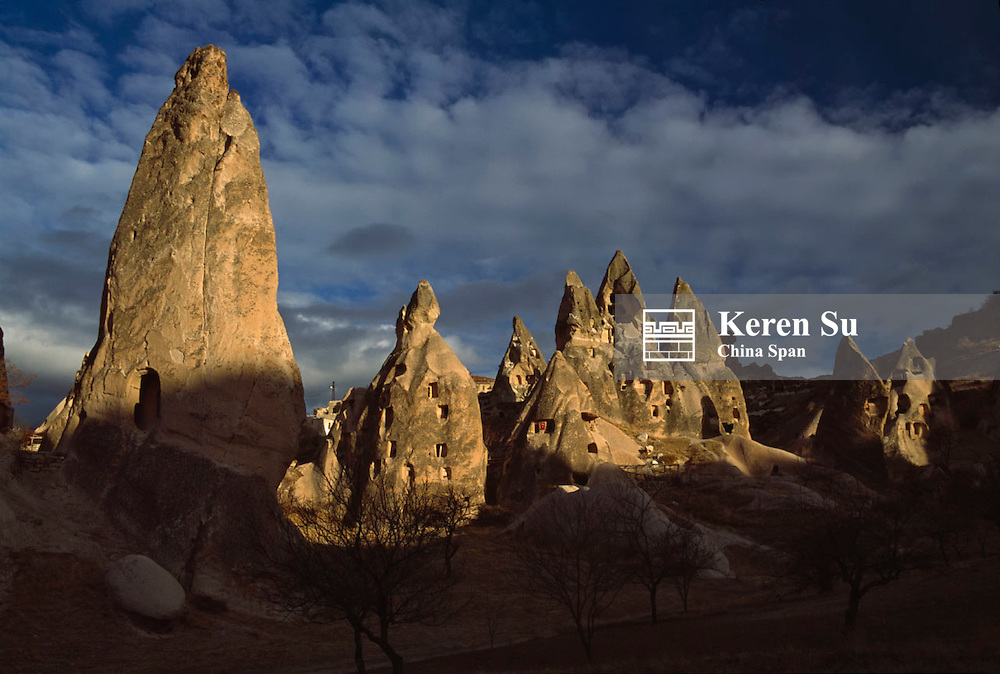 Homes cut into naturally formed volcanic pinnacles, at sunset, Cappadocia, Turkey