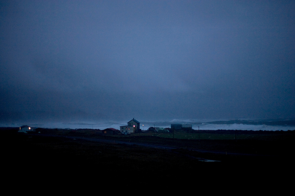 Iceland crisis, October 9, 2008..There is light in a couple of lone houses as the wind and waves ravage in the background.  On the outskirts of Grindavik in Iceland, a waves hits the shore...As of Thursday October 9th, the three largest banks in Iceland had been taken over by the Icelandic government. This makes Iceland the hardest hit European country of the global financial crisis of autumn 2008 effectively putting the country by some measure in an economic depression.