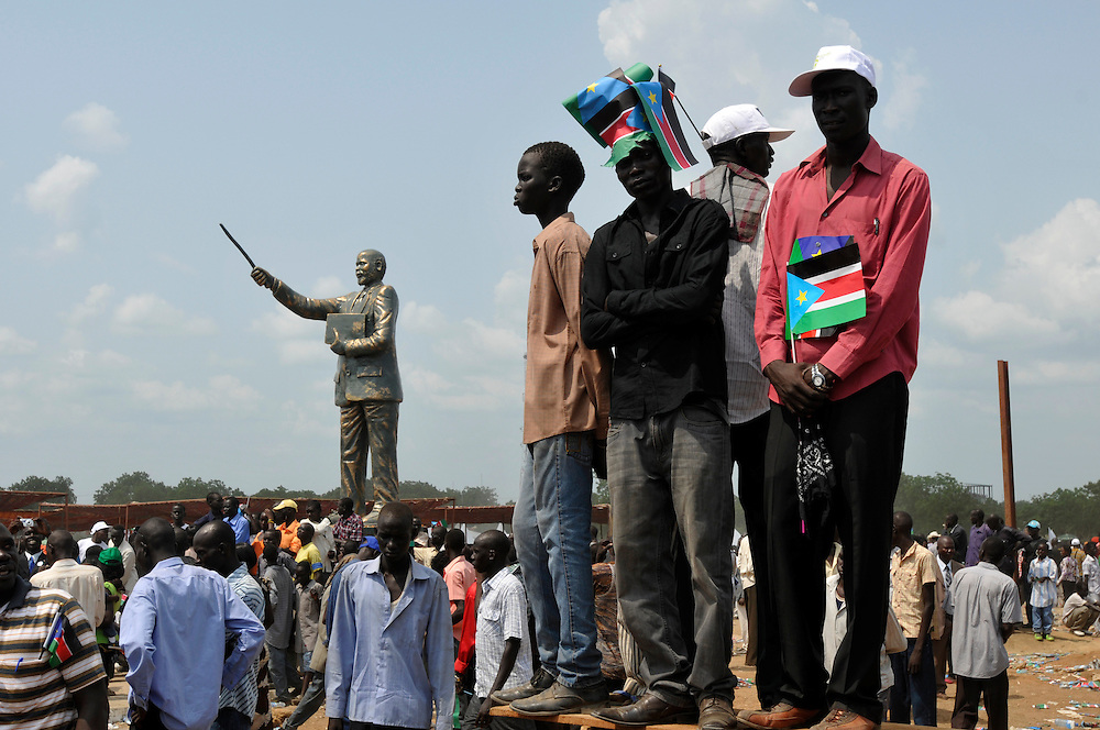 Young South Sudanese watch the official independence day ceremony next to a newly unveiled bronze statue of Dr. John Garang, the father of the country. After decades of conflict, Southern Sudan declared independence from the North on July 9th, 2011. Government officials, foreign dignitaries and ordinary people came to the John Garang Memorial in the capital from all over the country and the world to celebrate the historic occation..Juba, South Sudan. 09/07/2011..Photo © J.B. Russell