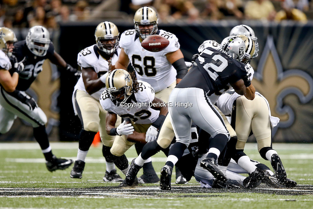 Aug 16, 2013; New Orleans, LA, USA; New Orleans Saints running back Travaris Cadet (39) fumbles against the Oakland Raiders during the second half of a preseason game at the Mercedes-Benz Superdome. The Saints defeated the Raiders 28-20. Mandatory Credit: Derick E. Hingle-USA TODAY Sports