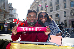 Spectators hold a Tommy's banner during the 2019 London Landmarks Half Marathon.