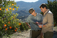 Farmer and man reading in orchard