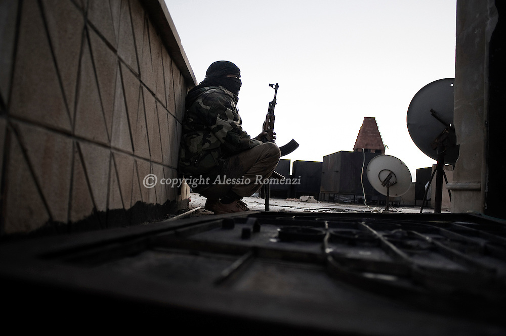 SYRIA - Al Qsair. A member of the Free Syrian Army takes cover from Al Assad Army snipers on the roof of the former police station in Al Qsair, on February 10, 2012. After a one day battle the Free Syrian Army manage to take the building. In the battle, 11 member of the Syrian police have been killed. ALESSIO ROMENZI