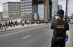 © Licensed to London News Pictures. 05/06/2017. London, UK. A City of London policeman watches as people use London Bridge for the first time following a terrorist attack in Saturday evening. Three men attacked members of the public  after a white van rammed pedestrians on London Bridge.   Ten people including the three suspected attackers were killed and 48 injured in the attack. Photo credit: Peter Macdiarmid/LNP