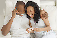 Couple examining pregnancy test in bed, man using mobile phone