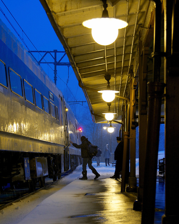 A traveler boards a New York bound train on a snowy night at Maplewood Station.