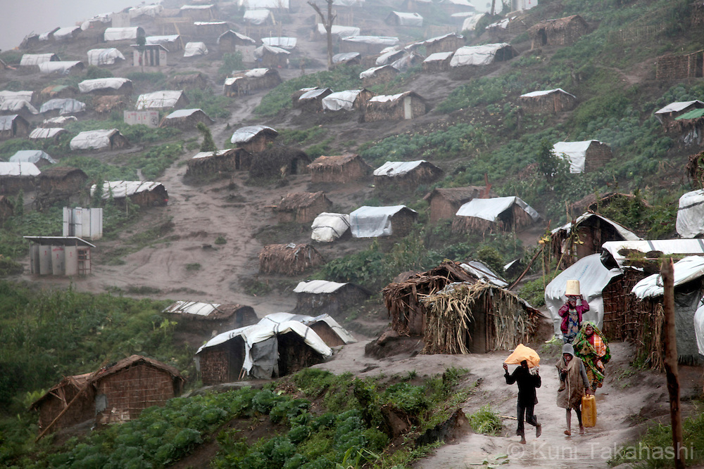 Refugees walk in rain at Mpati IDP camp, about 100 km northwest of Goma, DRC on April 23, 2010. The long war had involved 9 African nations and claimed an estimated three million lives as a result of fighting or disease and malnutrition..Photo by Kuni Takahashi