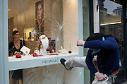 A student protester smashes a shop window in Piccadilly, central London as the shopkeepr looks on.