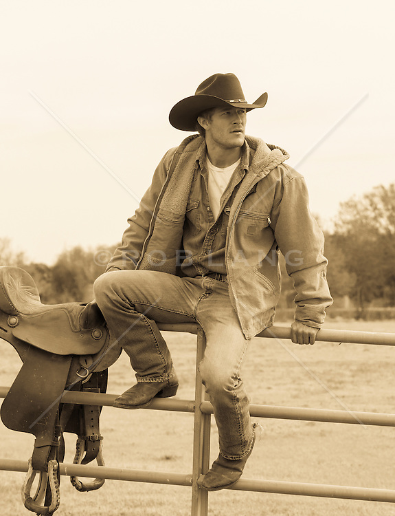 good looking cowboy sitting on a fence at a ranch